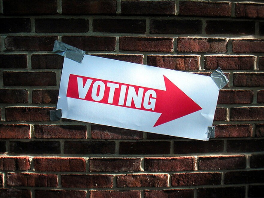 A white piece of paper taped on a brick wall. There is a red arrow on the paper with the word 'Voting' inside.