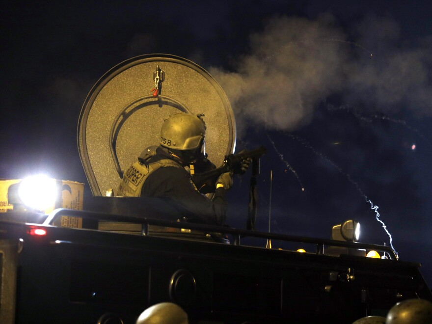 Police fire tear gas from an armored personnel carrier on Aug. 18 in Ferguson, Mo. The U.S. Senate is holding a hearing on the use of military-grade equipment by local police departments.