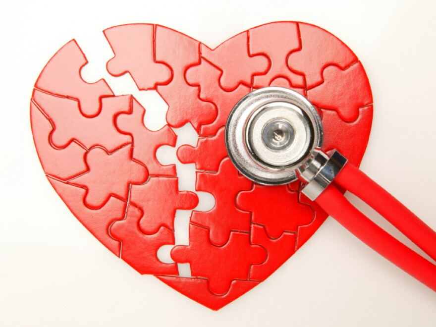 A stethoscope rests on top of a puzzle shaped like a heart.