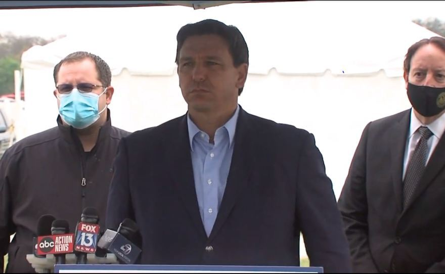 man speaks in front of microphones with two men wearing masks behind him
