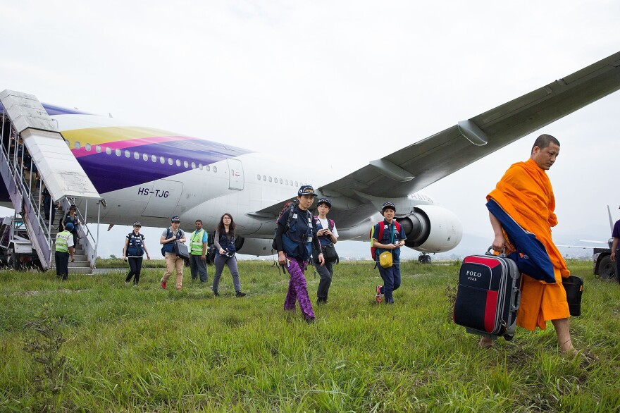 Monks and aid workers walk to the arrival terminal at Kathmandu's international airport. The plane was unable to secure an arrival gate when it landed on Wednesday.