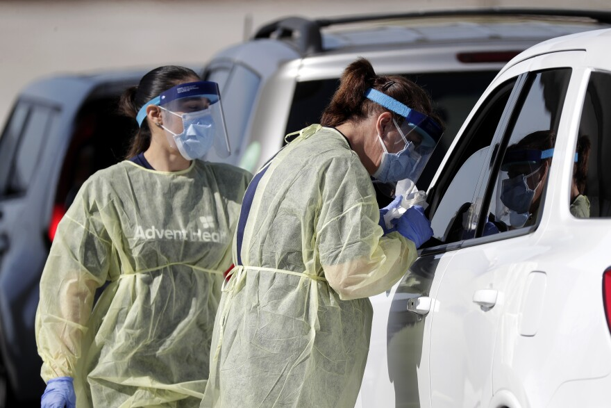 Healthcare workers conducts COVID-19 tests at a drive-thru coronavirus testing site, Tuesday, April 21, 2020, in Sanford, Fla.