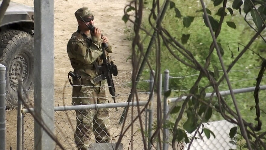 In this frame from a video, a member of the National Guard watches over Rio Grande River on the border in Roma, Texas, on Tuesday. The deployment of National Guard members to the U.S.-Mexico border at President Trump's request was underway Tuesday with a gradual ramp-up of troops under orders to help curb illegal immigration.