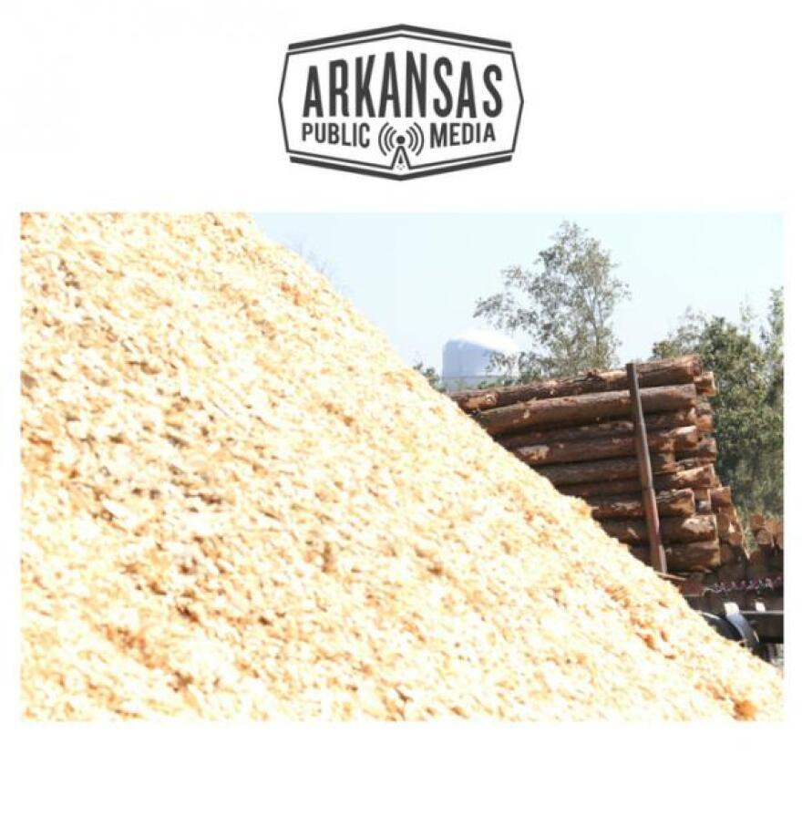 Logging trucks rumble by stockpiled mountains of freshly shaved wood chips scheduled for extrusion into biofuel at Highland Pellets in Pine Bluff.