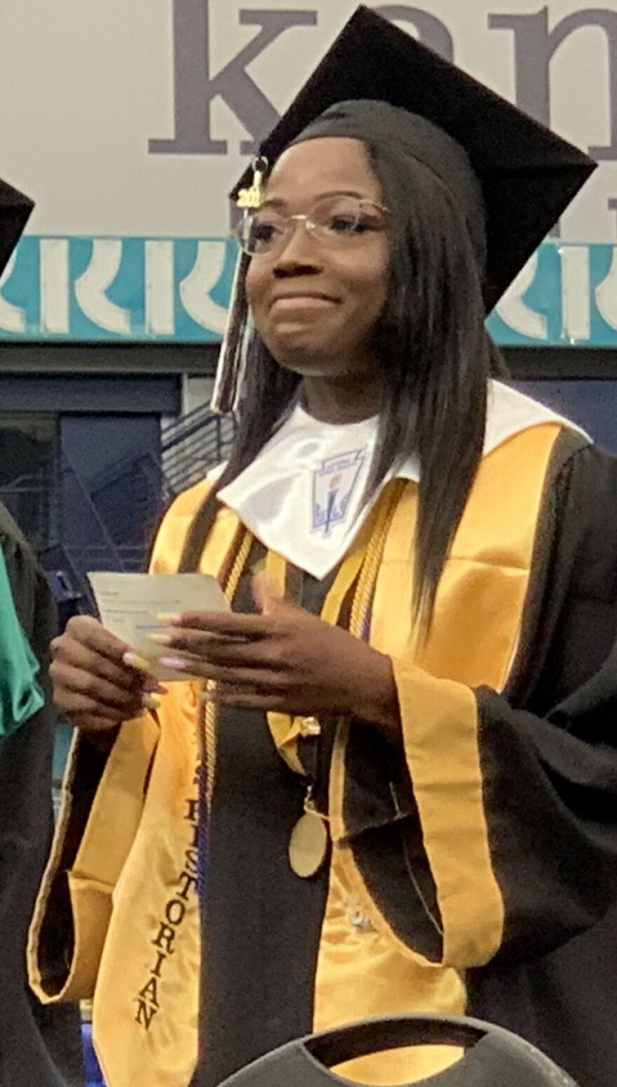 Shadine Henry smiles on stage at her graduation ceremony, May 25, 2019