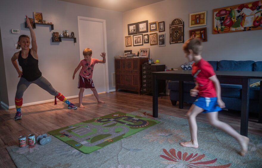Mimicked by her son Daniel (C), Paulina Mansz, a group fitness instructor, records a workout session for her clients while her other son Javier plays, as she continues to instruct from home in Arlington, Virginia on April 30, 2020. (Photo by ANDREW CABALLERO-REYNOLDS/AFP via Getty Images)