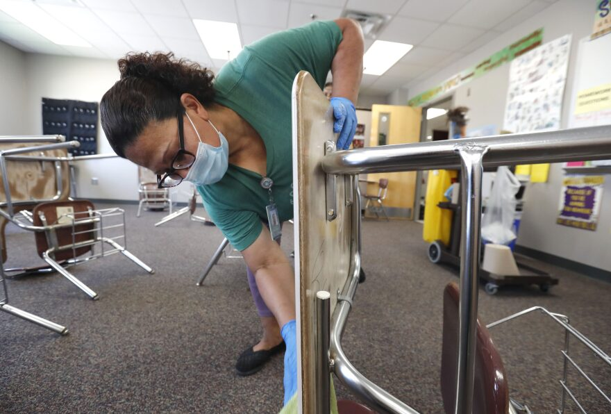 Josefina Median wears a mask as she cleans a classroom at Wylie High School Tuesday, July 14, 2020, in Wylie, Texas. (LM Otero/AP Photo)
