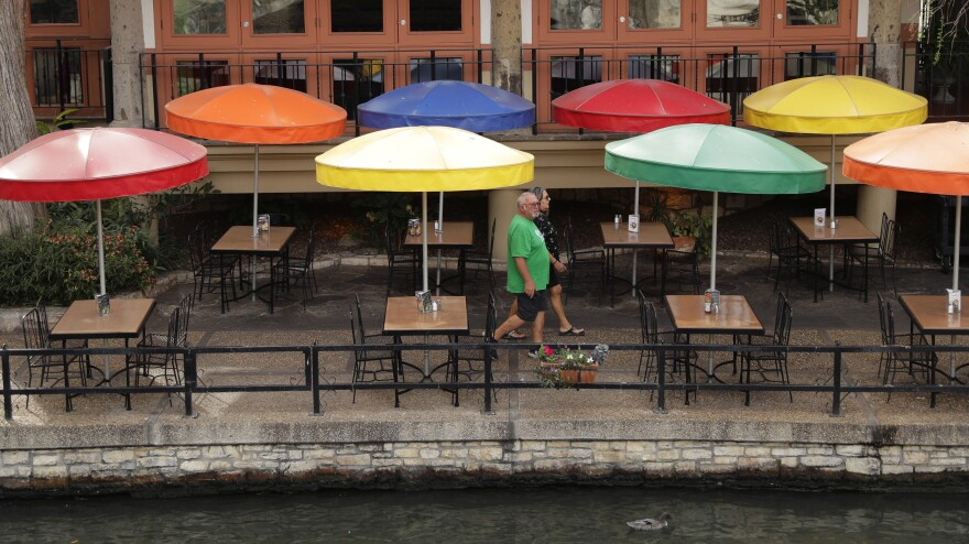 Visitors walk past a restaurant on the River Walk Monday in San Antonio.