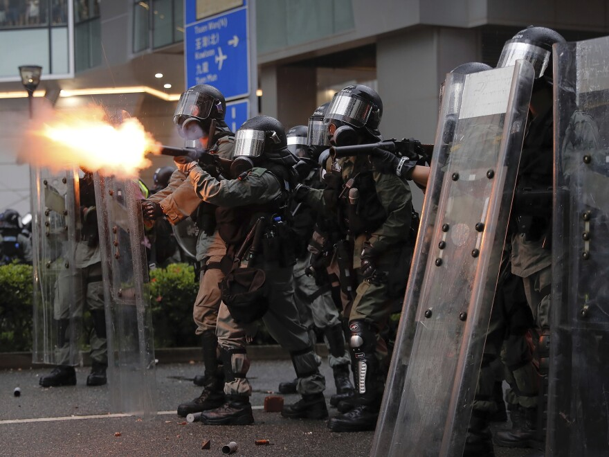 Riot police fire tear gas at protesters in Hong Kong on Aug. 25.