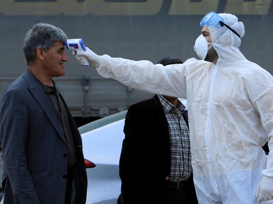 As the coronavirus that causes COVID-19 spreads to more areas, a health worker checks a man's temperature at a checkpoint on the outskirts of Duhok, Iraq, last Tuesday.