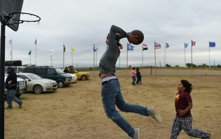 Evan Butcher of the Chippewa Tribe plays basketball with younger boys at an encampment near Cannon Ball, North Dakota.