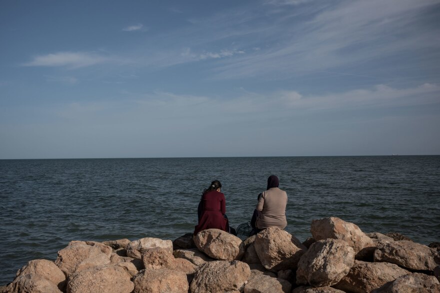People sit by the seaside looking north towards the Mediterranean Sea, in the town of Sfax.