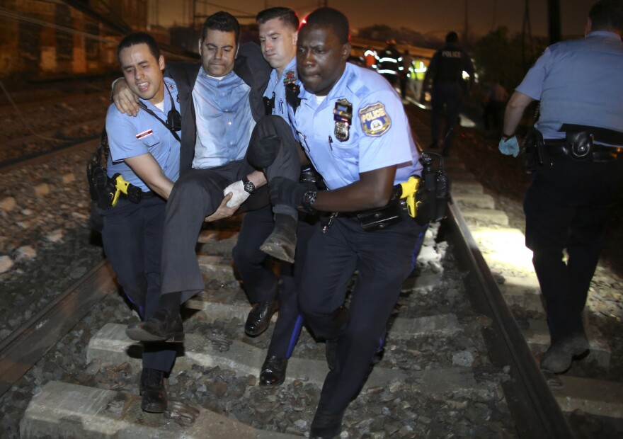 Emergency personnel help a passenger at the scene of a train wreck, Tuesday, in Philadelphia.