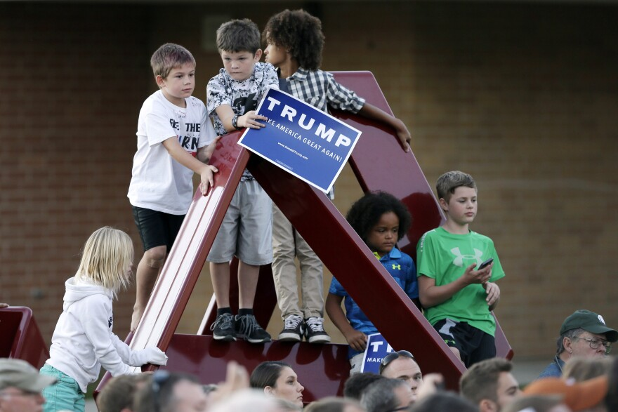 Children climb on a sculpture as Republican presidential candidate Donald Trump speaks during a rally at Urbandale High School in Urbandale, Iowa.