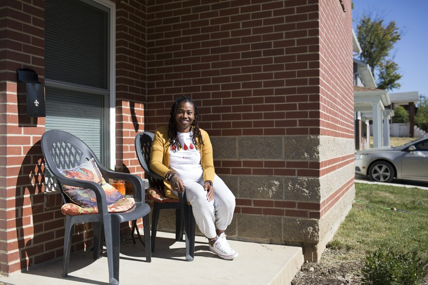 Mary Harris poses outside her new townhouse in Pine Lawn. Nonprofit group Beyond Housing built dozens of affordable homes in the area using a low-income housing tax credit. Oct. 7, 2019