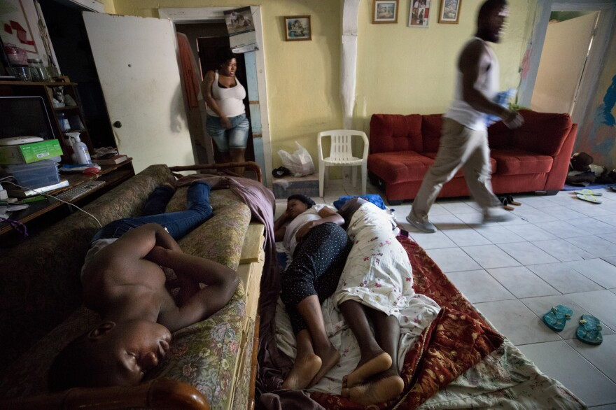 From left: Justin Bain, Sherrine Petit Homme LaFrance and Ferrier Petit Homme have little space to sleep in the family home of China and brother Odne Laguerre, who have taken in 10 Haitian evacuees from Abaco.