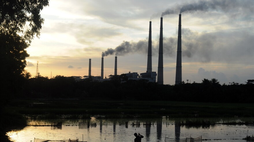 The chimneys of the Kolaghat Thermal Power Station loom above a field flooded for rice farming near Mecheda, West Bengal, India, in July 2011.
