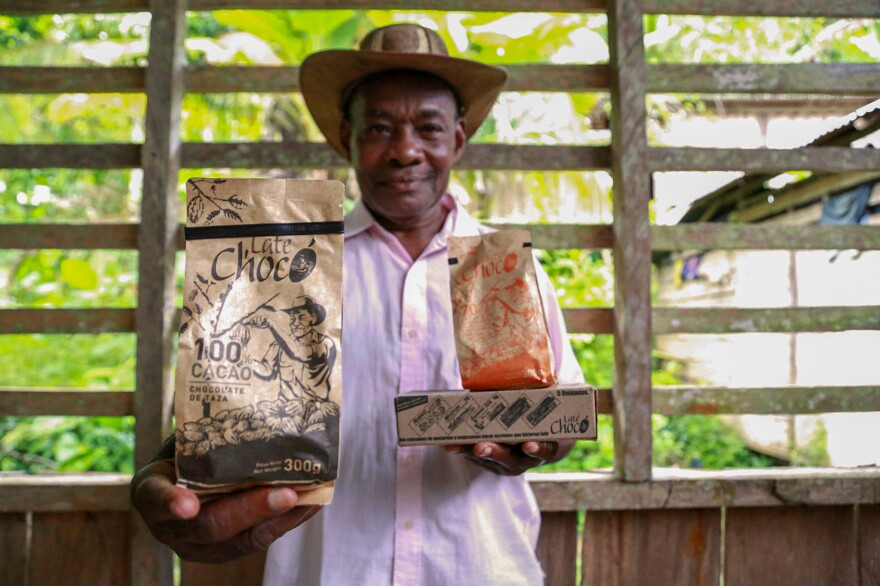José Palacios, a cacao farmer, holds the Late Chocó chocolate products produced by his son, Joel, in Bogotá. The package bears an illustration of his likeness. José Palacios lives in Colombia's western Chocó department, which is also a coca-growing region.