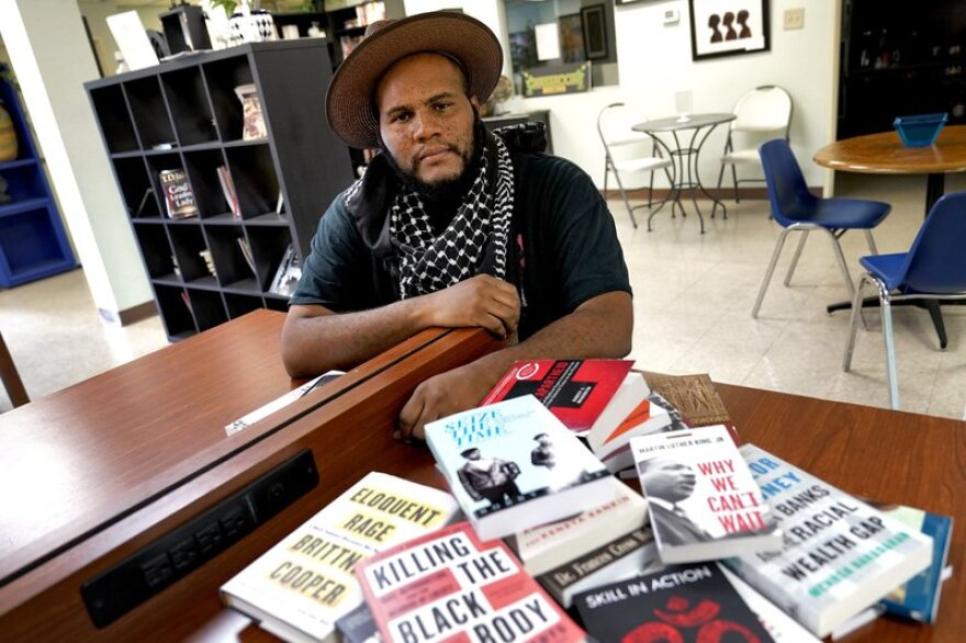 A photo of Black-bookstore owner Ali Nervis surrounded by books