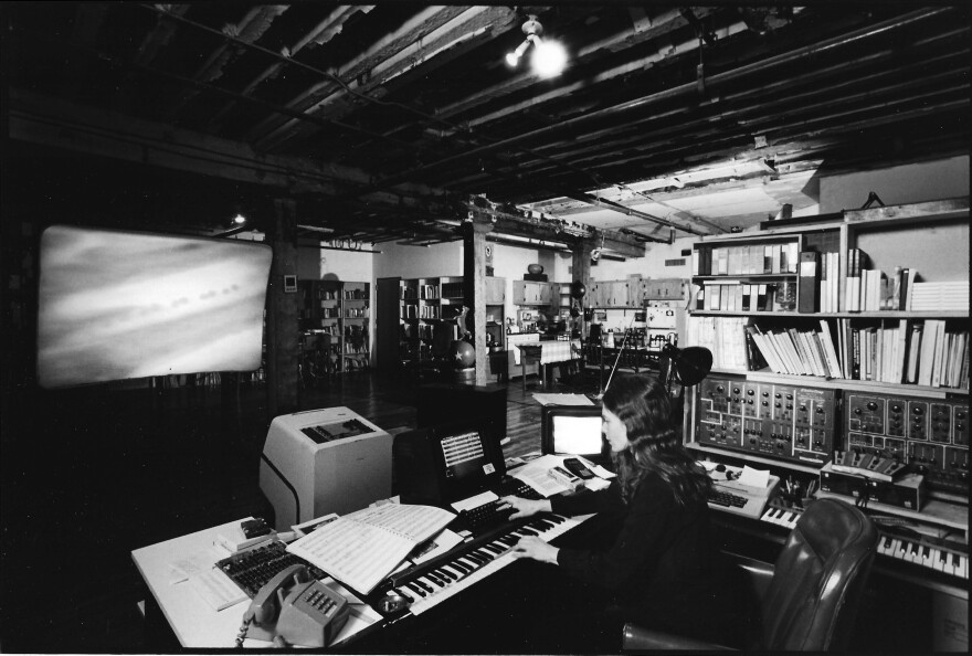 Laurie Spiegel in 1985, with footage of NASA's first Jupiter fly-by projected on the screen in front of her. After twice losing access to tools she used to make her music, Spiegel invented a computer program called Music Mouse that she used to create her 1991 album <em>Unseen Worlds</em>, which was reissued this year.