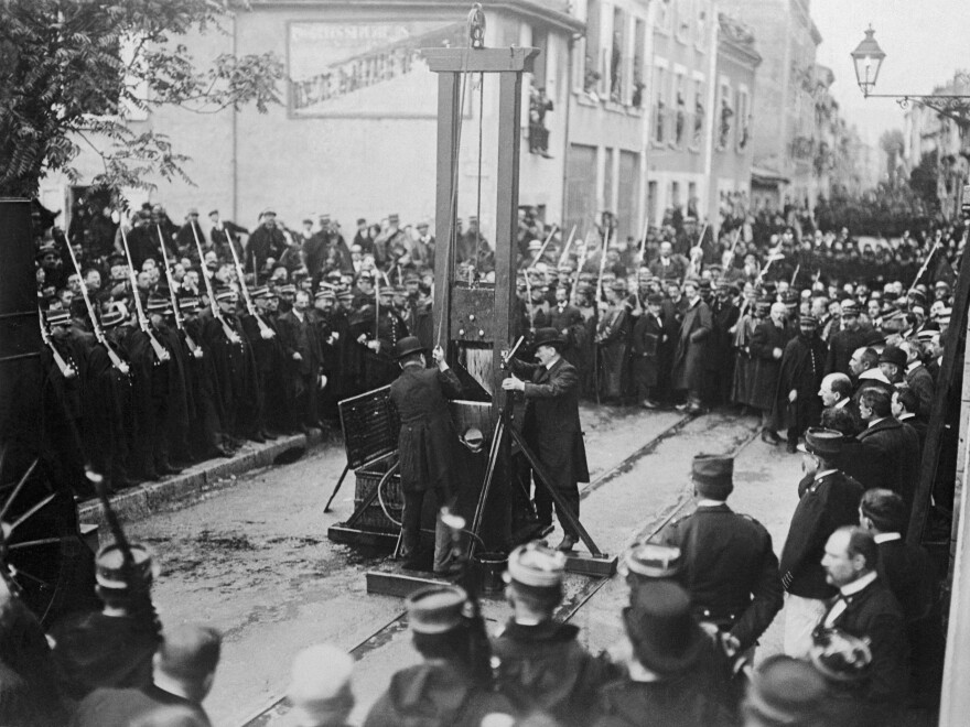 A photo dated 1929 of an execution by guillotine somewhere in France.