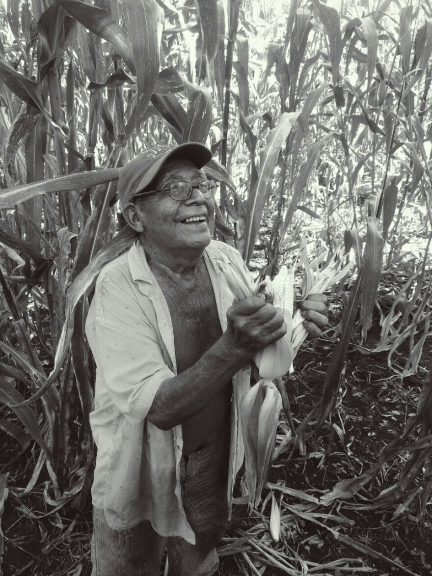 Dionisio Yam Moo beams while shucking corn that he harvested in October, 2016.