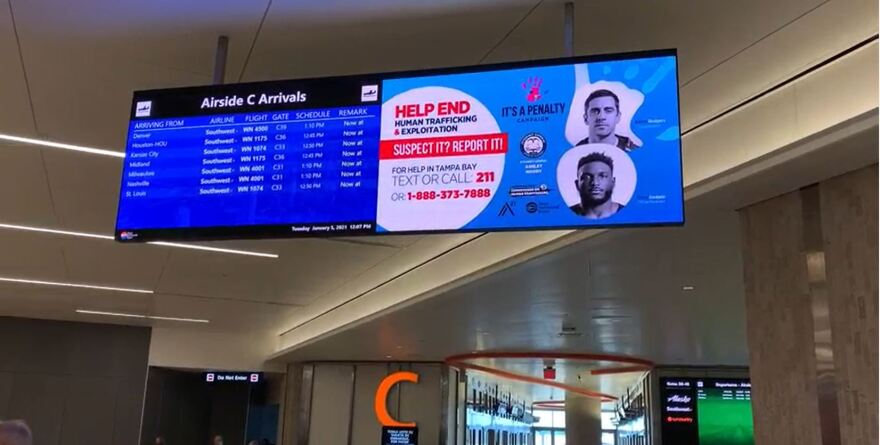 A digital sign hangs in an airport, showing an advertisement to combat human trafficking