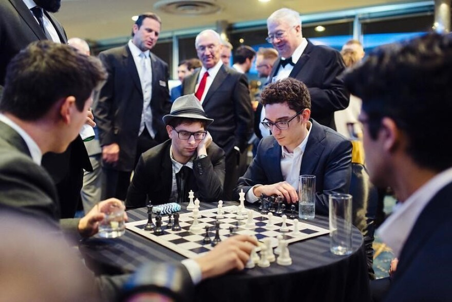 Fabiano Caruana, Eric Rosen and Denes Boros play chess during the cocktail hour at the 2018 Strategy Across the Board gala.