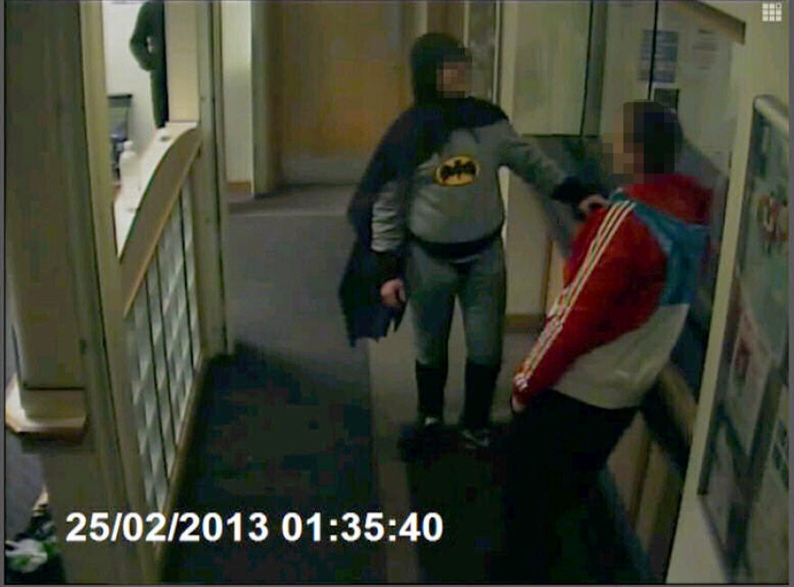 Batman brings in a wanted man to a police department in England.