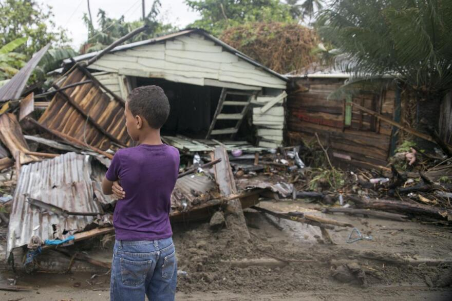 A boy stand outside his family's wrecked home in the Dominican Republic after Hurricane Irma in 2017.
