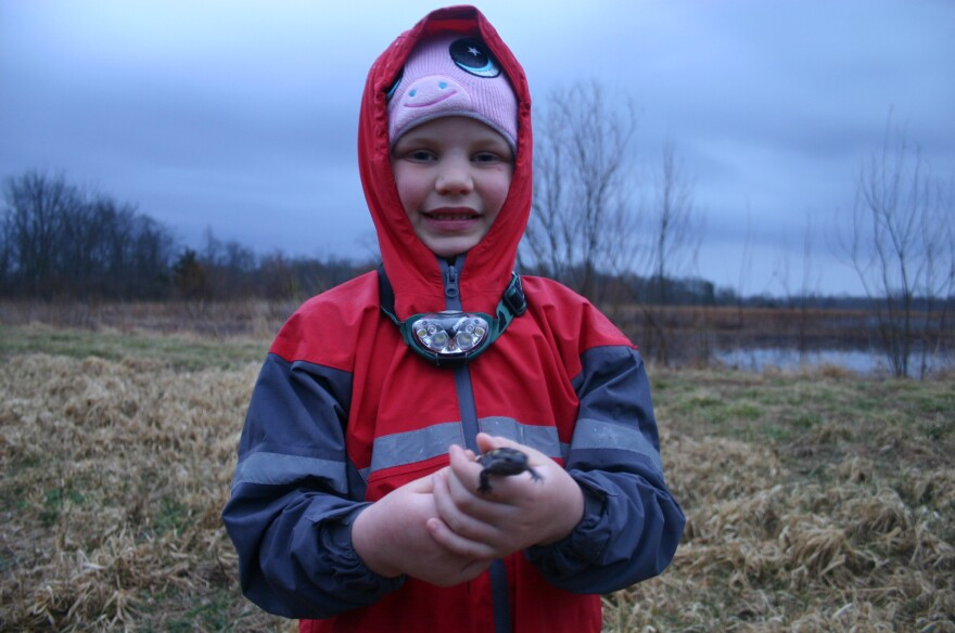 Calliope Messerschmitt holding a yellow spotted salamander just before dusk next to the vernal pool at Caesar Creek State Park