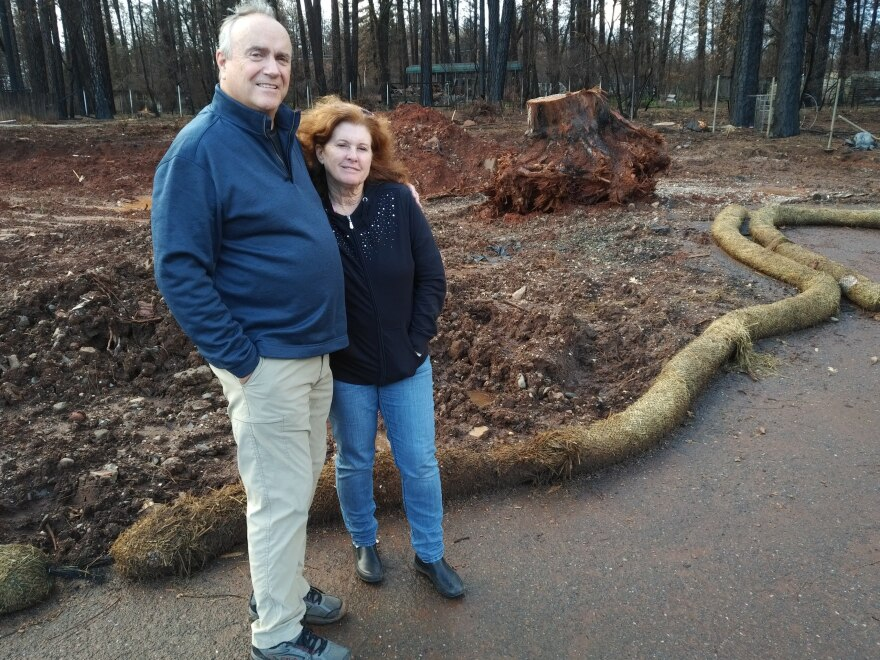 Jim and Colleen Corner standing on the lot where their two-story house burned down in November's Camp Fire. They are already starting to re-build.