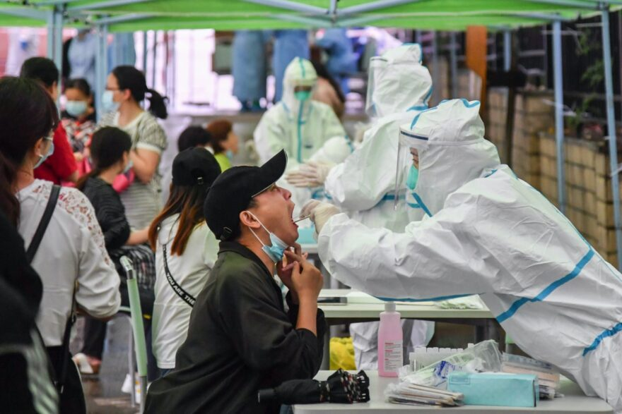 A medical worker takes a swab sample from a resident to be tested for the COVID-19 coronavirus in Wuhan in China's central Hubei province on May 14, 2020. - Nervous residents of China's pandemic epicentre of Wuhan queued up across the city to be tested for the coronavirus on May 14 after a new cluster of cases sparked a mass screening campaign.
