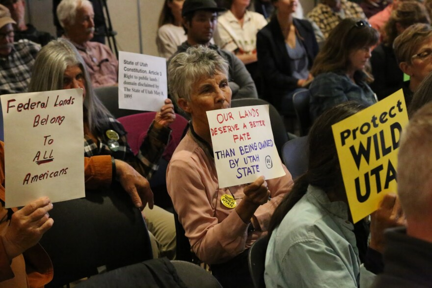 "Photo of a woman with a sign that says ""our lands deserve a better fate than being owned by Utah state."""