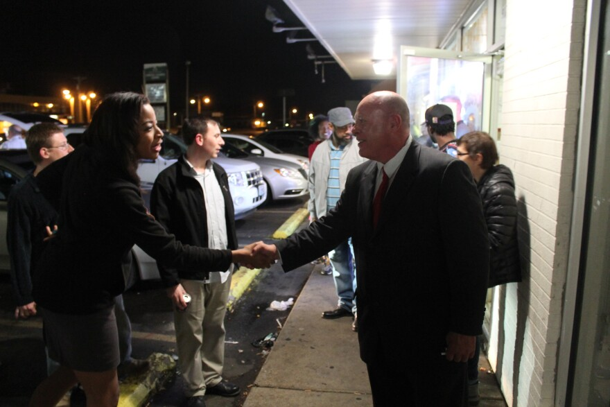 Bob Hudgins shakes the hand of a television reporter on Tuesday at the Ferguson Burger Bar.
