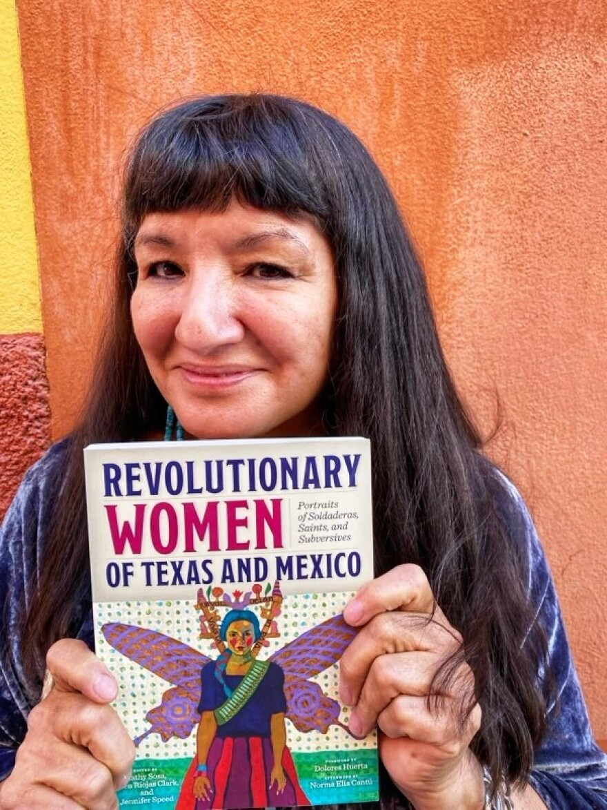 """Author Sandra Cisneros, with long black hair and thick bangs, holding the book """"Revolutionary Women of Texas and Mexico."""""""
