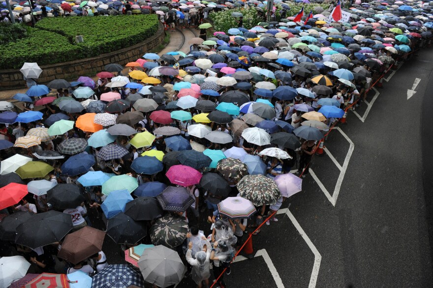 Protesters use umbrellas to deflect the rain Tuesday during a march and rally seeking greater democracy in Hong Kong.