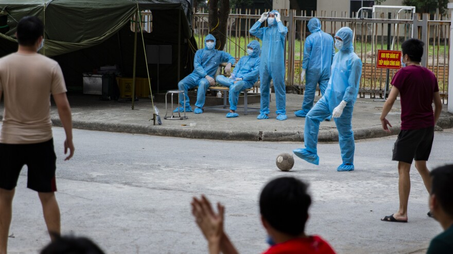 A health worker plays goalkeeper in a pick-up soccer game with quarantined residents, who make an effort to maintain an appropriate distance from each other as they play.<strong></strong>