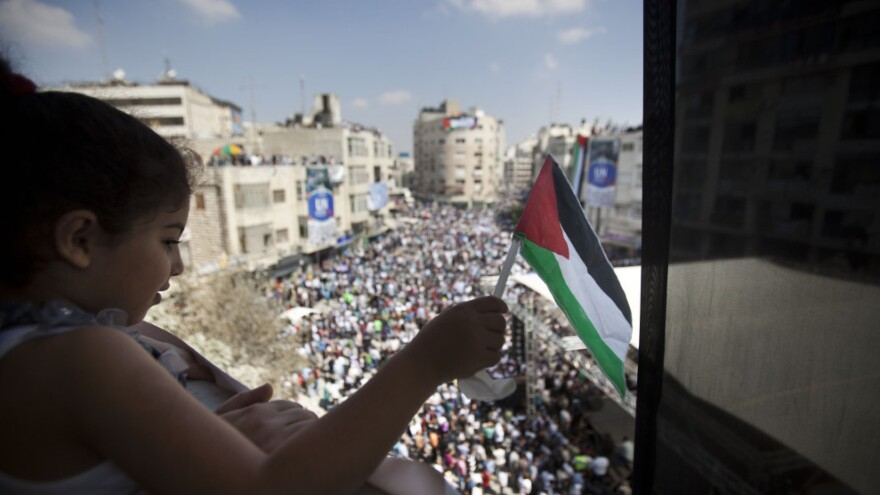 A Palestinian girl in Ramallah, West Bank, waves a flag Wednesday during a demonstration in support of the Palestinian bid for recognition of statehood at the United Nations. Palestinian President Mahmoud Abbas is expected to submit a letter to the U.N. Security Council to petition for statehood during the U.N. General Assembly.