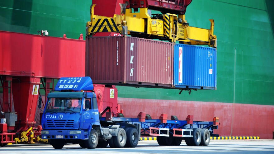Containers are transferred at a port in Qingdao in China's eastern Shandong province on July 6. China has announced a plan to impose more tariffs on U.S. goods, in response to escalating trade threats from the Trump administration.