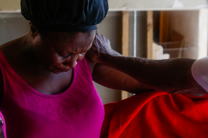 Remelda Thomas bows her head in prayer within her home in McLean's Town Grand Bahama on September 16, 2019. Thomas said she lost eight family members in the storm. While sleeping one night after the storm the wind was blowing and the tarp over the hole in