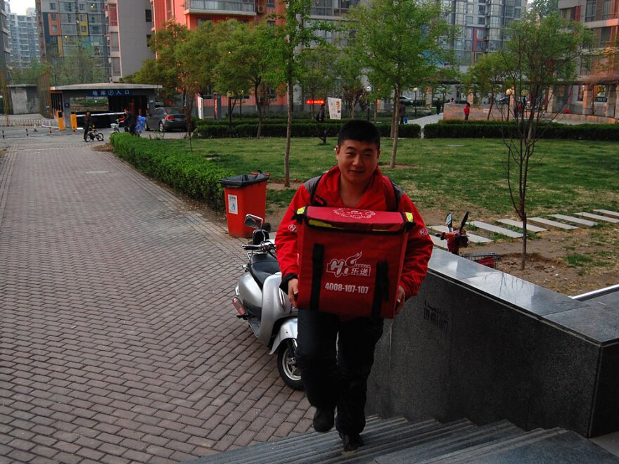 Haidilao delivery man Liu Lei rides an electric moped to a customer's house, with two backpacks — one with the food, one with the hot plate, pot and utensils. He arrives one hour after the order was placed.