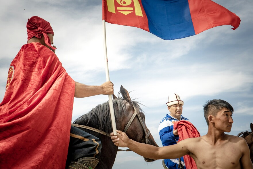 A member of the Mongolian horse wrestling team passes a flag to another member who is preparing for a victory lap around the stadium after a match victory.
