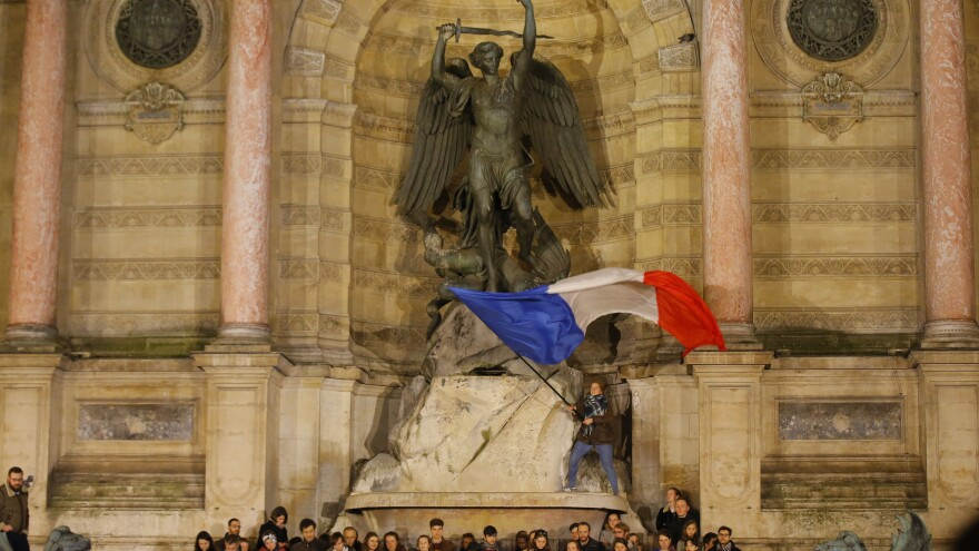 People attend a vigil in Paris on Tuesday near the fire-damaged cathedral.