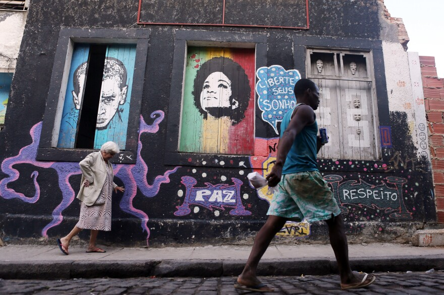 People walk past graffiti art in the Providencia community of Rio, a favela that dates back to 1897.