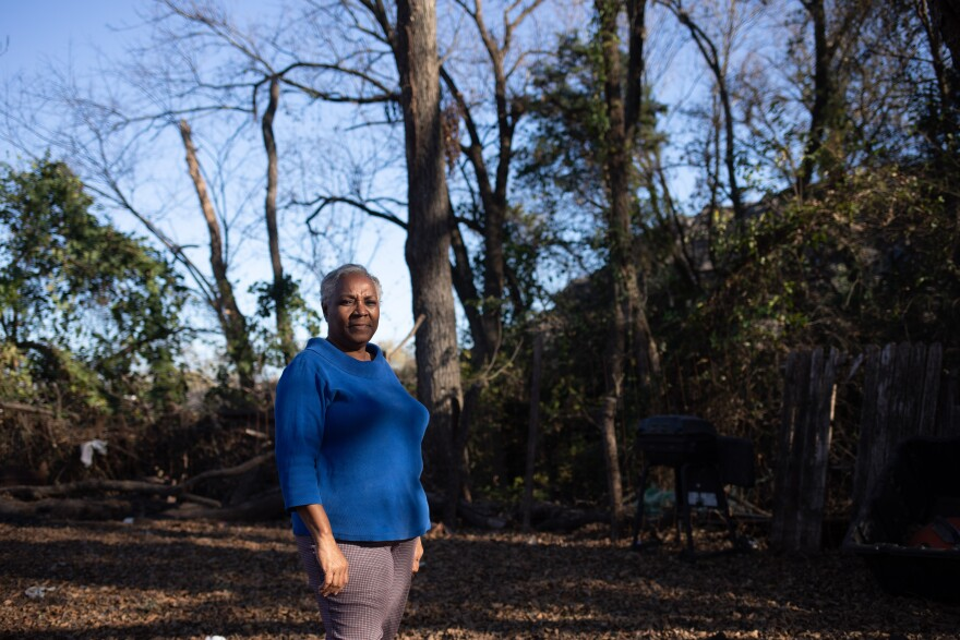 Marsha Jackson stands in her backyard, where Shingle Mountain towers in the background. Jackson has been fighting for the removal of the toxic waste dump since 2018.