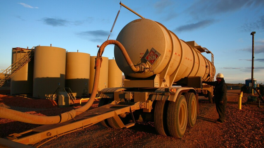 Keith Ceynar transfers oil from his truck into a tank at a facility outside Alexander, N.D. An increasing amount of oil is being delivered by trucks.