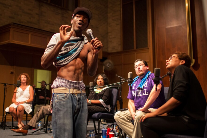 Ferguson resident Frankie Edwards shows a rubber bullet wound he suffered during one of the nights of protests to NPR's Michel Martin (right) and Ferguson Mayor James Knowles (second from right) during the community conversation at Wellspring Church.