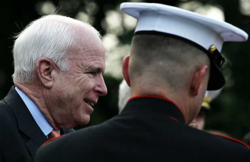 Arizona Senator John McCain is escorted to his seat during the weekly Marine Corps Sunset parade at the Marine Corps War Memorial Aug. 3, 2009.