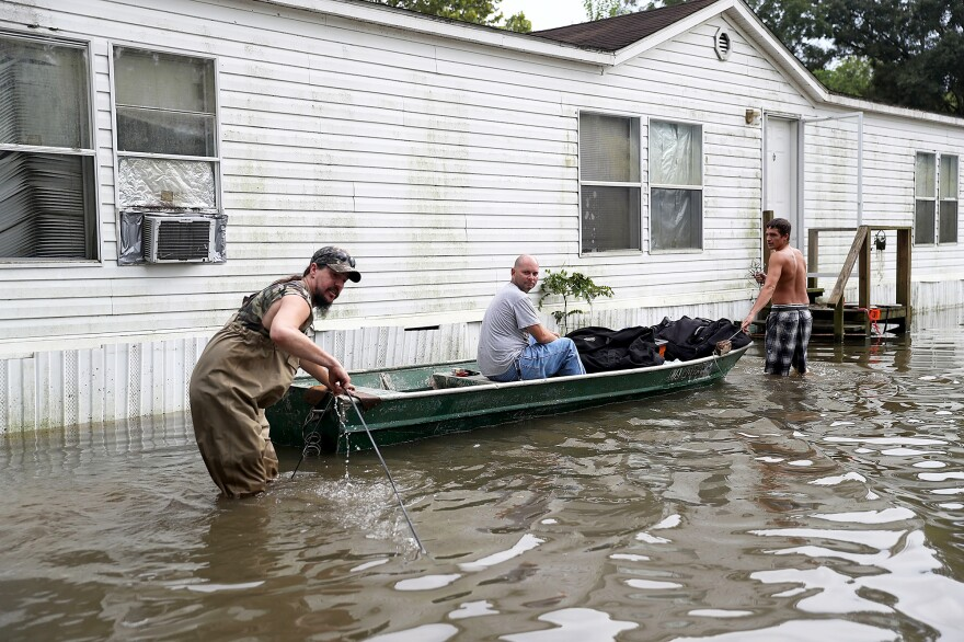 (Left to right) Billy Blazier, Randy Diez Jr. and Tray Blazier checked in on Billy's flooded home on Aug. 18 in Sorrento, La. Many storm sewers nationally simply weren't built to handle the sort of intense rainfall that seems to be happening with greater frequency, flood managers say.